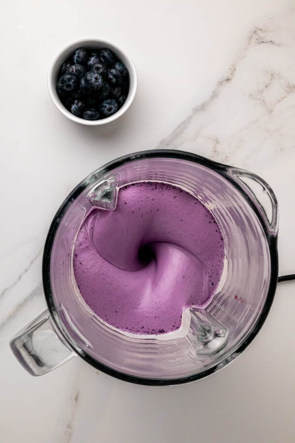 Blending the blueberries until the mixture goes purple