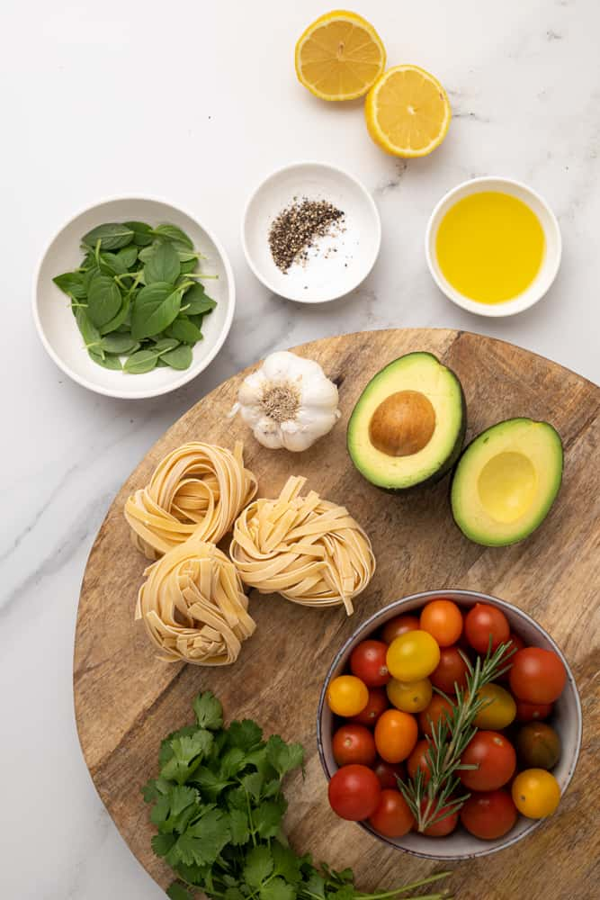 Raw ingredients for a green pasta on a wooden board