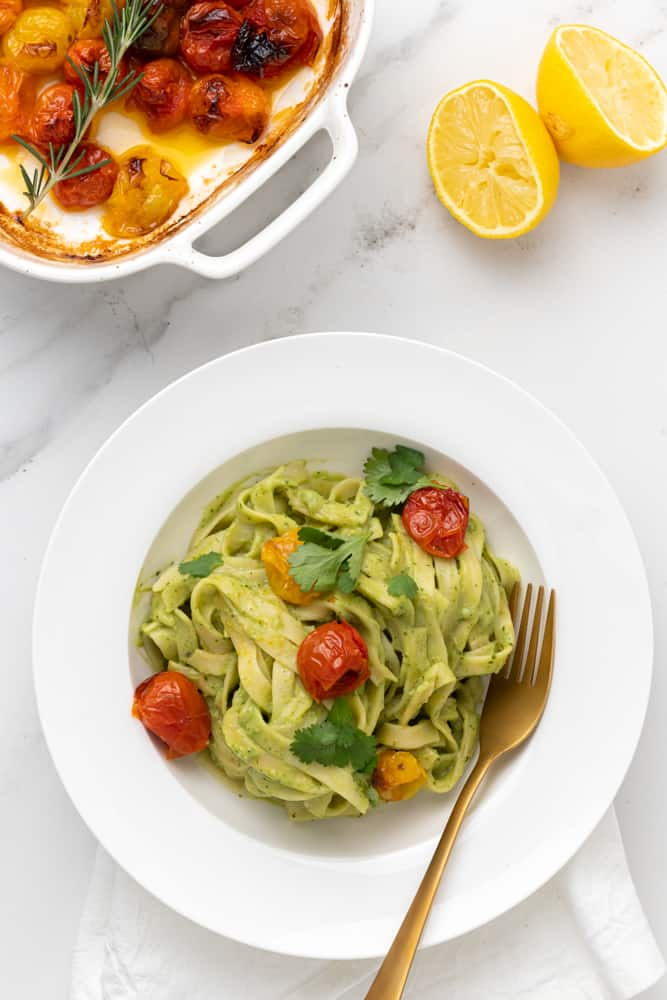 Served green pasta with roasted tomatoes and freshly sliced lemon